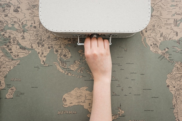 Vintage world map background with hand grabbing a suitcase Free Photo