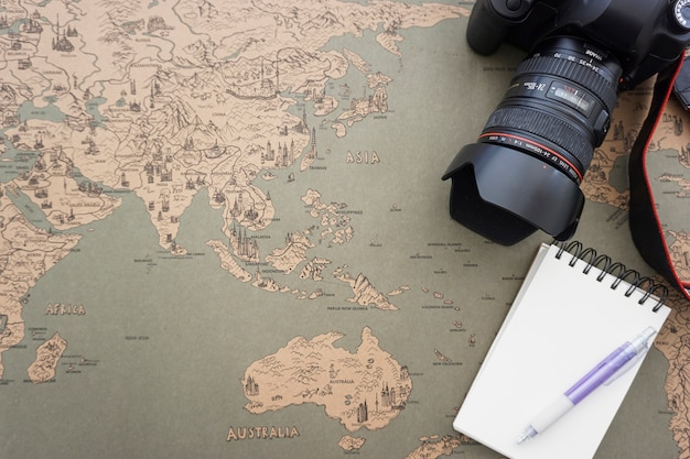 Vintage world map background with notebook camera and pen photo vintage world map background with notebook camera and pen free photo gumiabroncs Choice Image