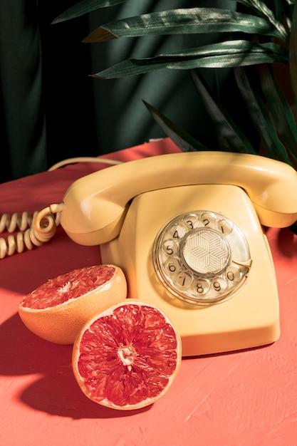 Vintage yellow telephone next to halved grapefruit Free Photo