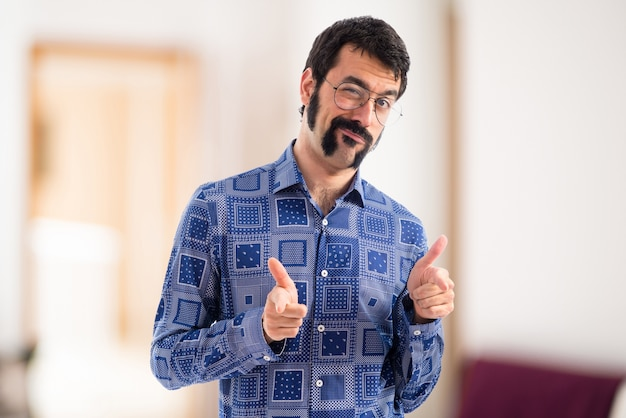 Vintage young man pointing to the front on unfocused background Premium Photo