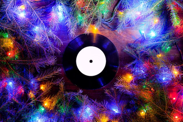 Vinyl gramophone record in christmas style for christmas playlist flat view with christmas lights Premium Photo