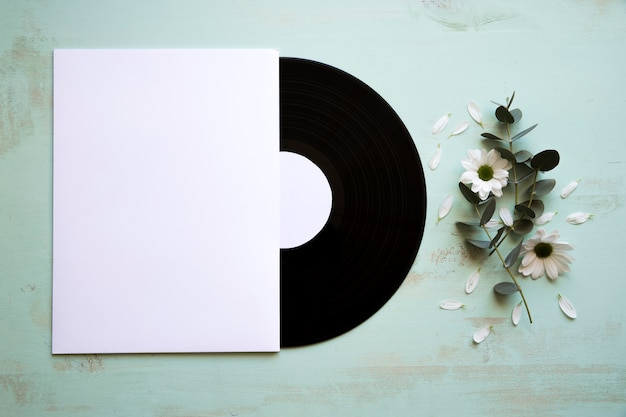 Vinyl and paper mockup next to flower Free Photo