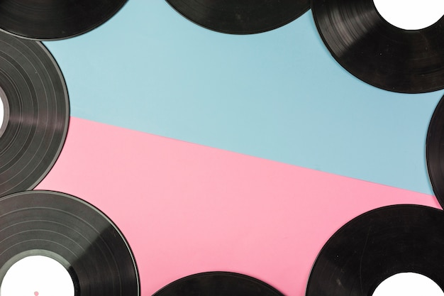 Vinyl records border on dual blue and pink background Free Photo