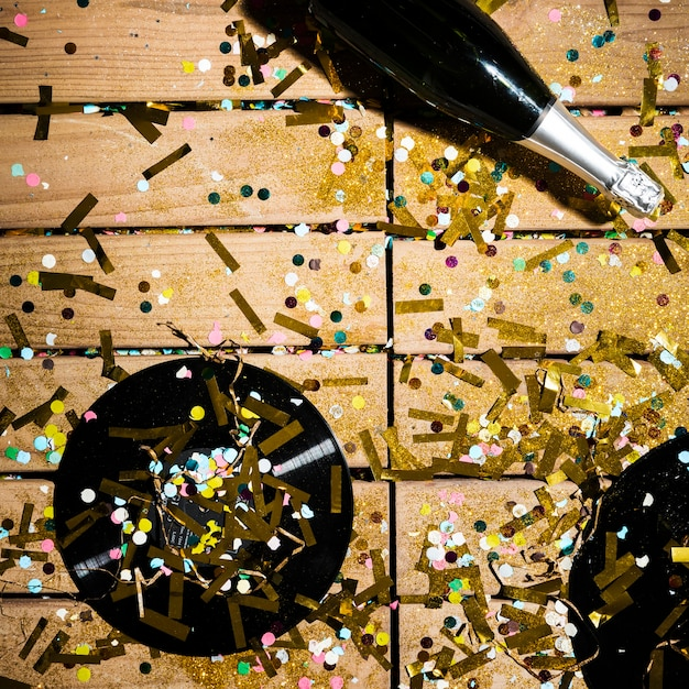 Vinyl records and bottle of drink between bright confetti Free Photo