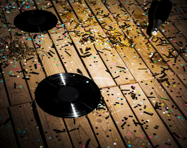 Vinyl records and bottle of drink between confetti Free Photo