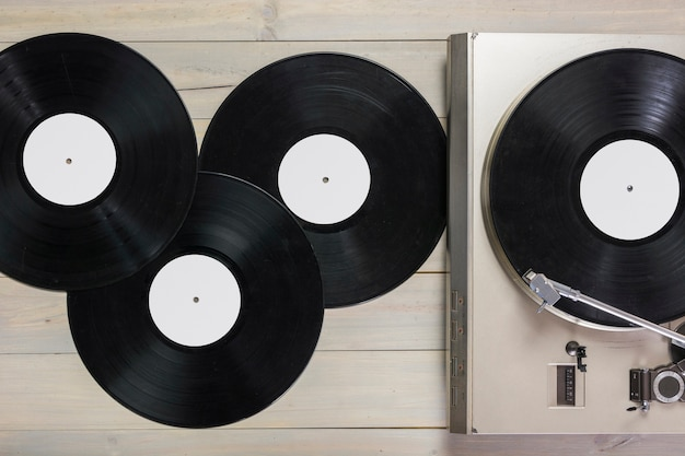 Vinyl records and turntable vinyl record player on wooden table Free Photo