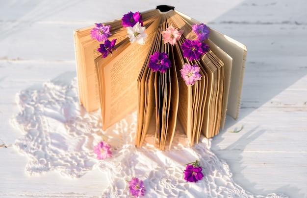 本の上の紫の花gelichrysum。木製の古いテーブルの上に透かし編みのテーブルクロス。村での夜。屋外の夕日、バタニカ、ガラスの美しい花。 Premium写真
