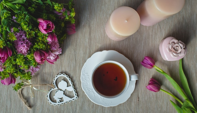 Violet tulips, pink aroma candles and a cup of tea Free Photo