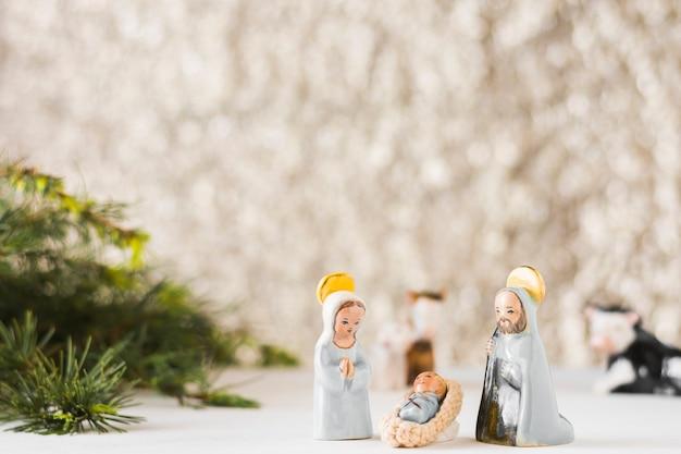 Virgin mary with baby jesus and saint joseph near fir tree Free Photo