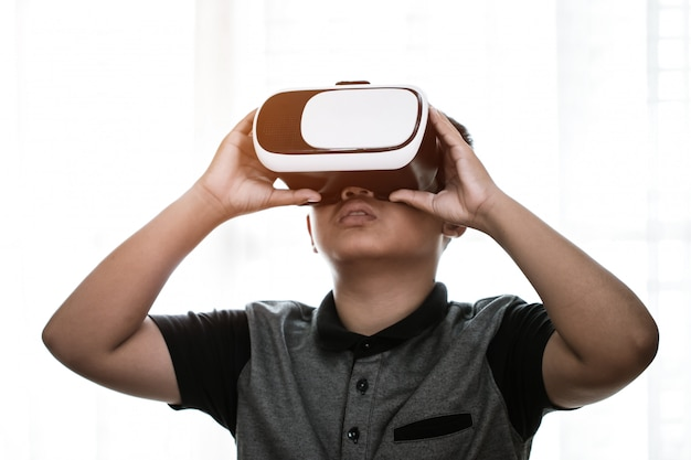 Virtual reality interaction headset by asian student wearing vr box over technology digital hud screen Premium Photo