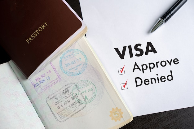 Visa and passport to approved stamped on a document top view Premium Photo