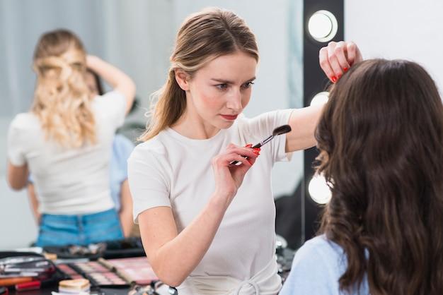 Visagiste doing makeup for young woman Free Photo