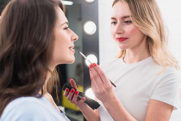Visagiste making lip makeup to client Free Photo