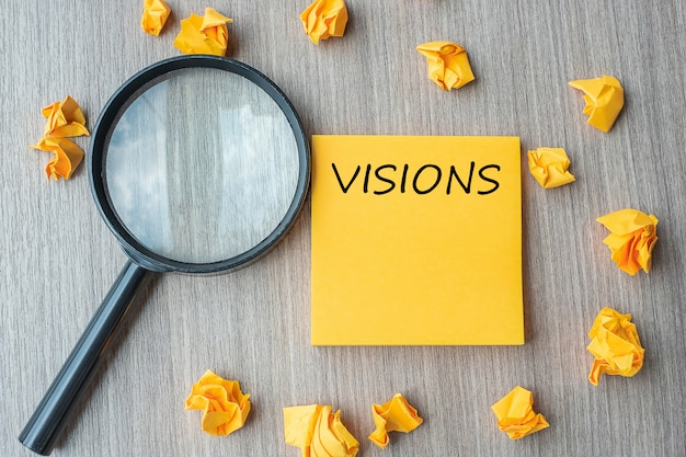Vision words on yellow note with crumbled paper and magnifying Premium Photo