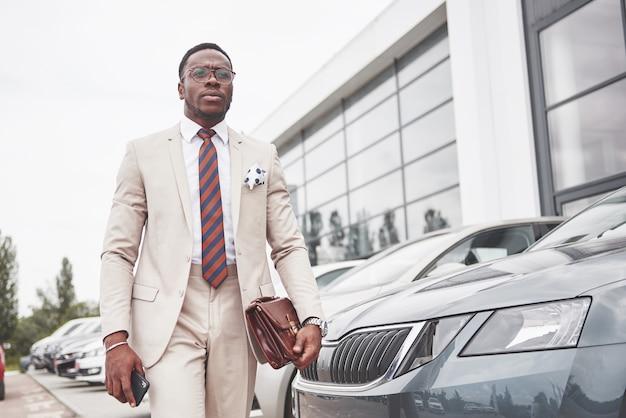 カーディーラー訪問。車の近くのスーツでカジュアルな黒のビジネスマン。 無料写真