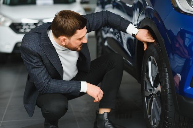 カーディーラー訪問。ハンサムなひげを生やした男は彼の新しい車をなでると笑顔 Premium写真