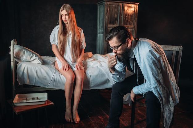 病院のベッドで病気の女性に対して座っている訪問者 Premium写真