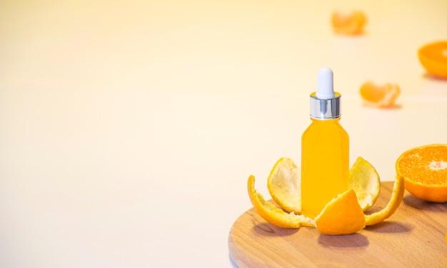 Косметическая бутылка сыворотки витамина c в кожуре мандарина с кусочками апельсина на белом фоне с копией пространства. Premium Фотографии