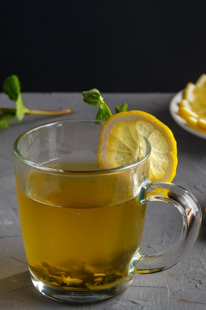 Vitamin ginger drink with honey mint and lemon in a glass cup on a concrete background vertical photo Premium Photo