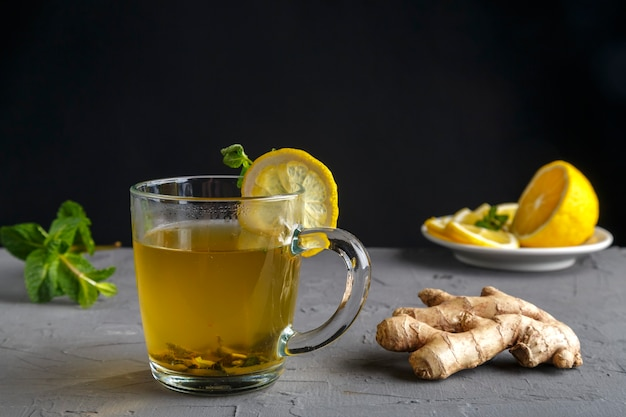 Vitamin ginger drink with honey mint and lemon in a glass cup near ginger root and lemon on a concrete background. horizontal photo Premium Photo