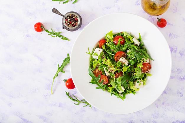 Витаминный салат из свежих помидоров, рукколы, сыра фета и перца. диетическое меню. правильное питание. вид сверху. квартира лежала. Бесплатные Фотографии