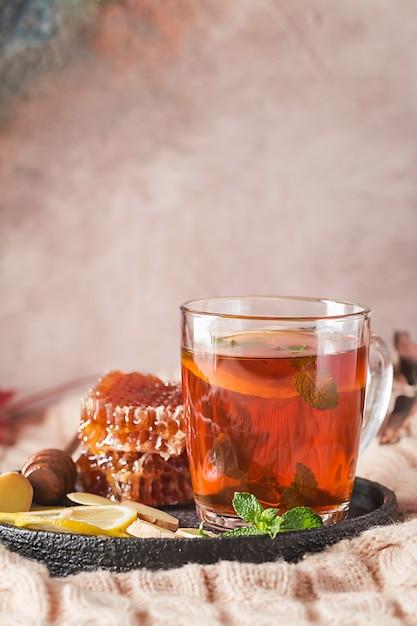 秋の背景を持つガラスカップのビタミンの健康的な海クロウメモドキ茶 Premium写真