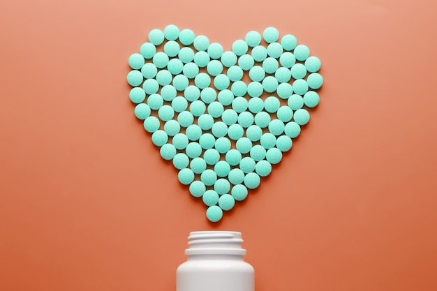 Vitamins b 12 on a red heart-shaped substrate, poured out of a white jar. Premium Photo