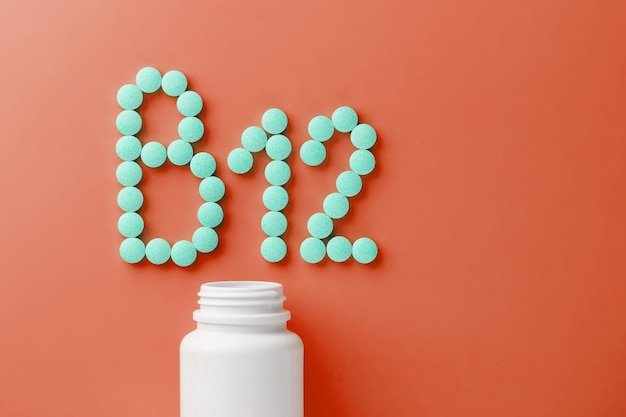 Vitamins b 12 on a red substrate, poured out of a white jar. Premium Photo