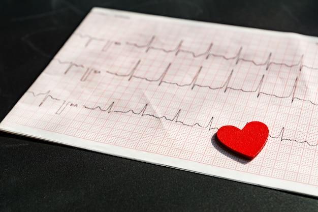 紙フォームvith赤い木製ハートの心電図のクローズアップ。黒のecgまたはekg紙。医療とヘルスケアの概念。 Premium写真