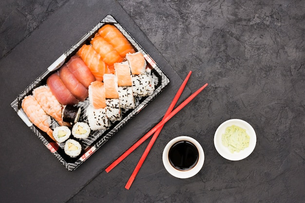 Vivid asian fish rolls on tray and chopsticks with soya sauce and wasabi over back concrete floor Free Photo