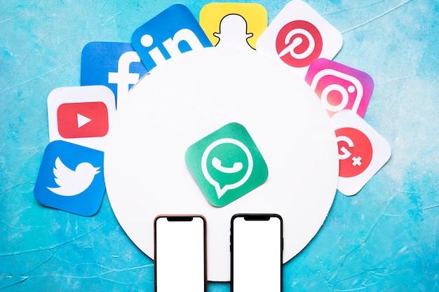 Яркие иконки сетевых приложений с двумя мобильными телефонами на синей стене Premium Фотографии