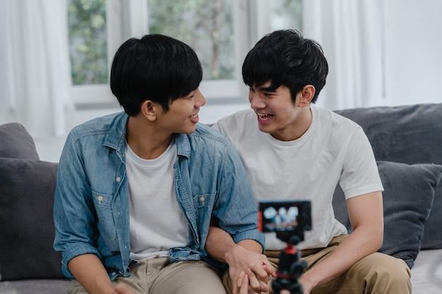 若いアジアの同性愛者カップルインフルエンサーカップルの自宅でのvlog。 10代の韓国lgbtq男性は、家のリビングルームでソファに横たわっている間、ソーシャルメディアでカメラの記録ビデオログのアップロードを使用して楽しいリラックスを楽しんでいます。 無料写真