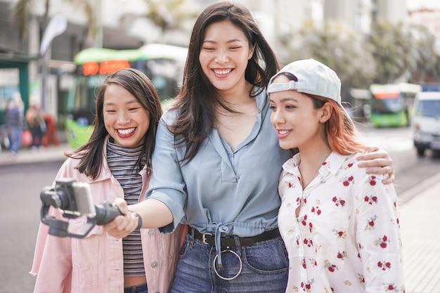 Счастливые азиатские девушки делая видео vlog на автобусной станции. модные друзья в социальных сетях Premium Фотографии