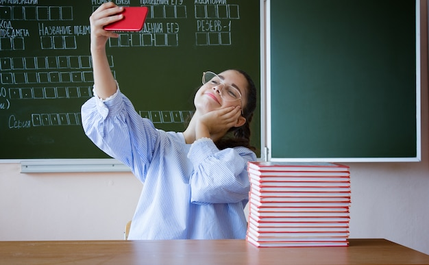 Vlogger stream online. student siting against blackboard with phone Premium Photo