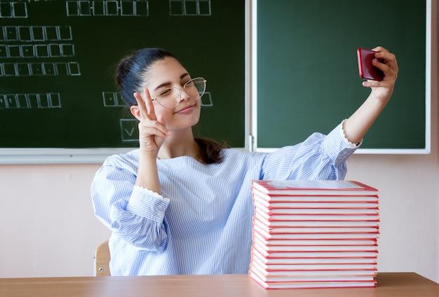 Vloggerストリームをオンラインで。教室で黒板に対して立地し、勝利のサインをしている学生 Premium写真