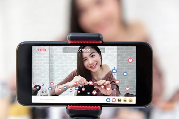 Азиатская женщина красоты vlogger обменивается макияж учебник видео в социальных сетях Premium Фотографии