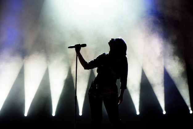 Vocalist singing to microphone. singer in silhouette Premium Photo
