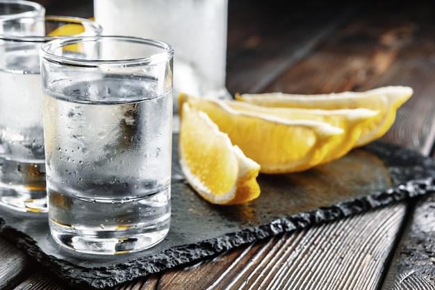 Vodka in shot glasses on rustic wood background Premium Photo