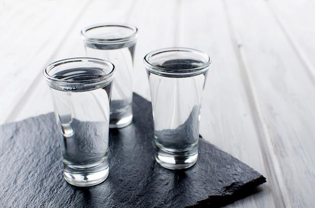 Vodka shots on white table Premium Photo