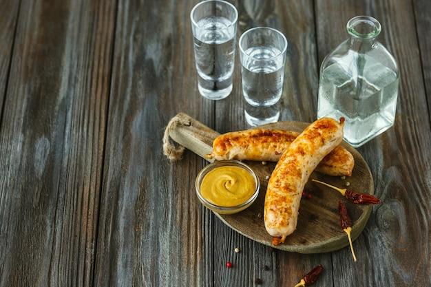 Vodka con salsicce fritte e salsa sul tavolo di legno Foto Gratuite