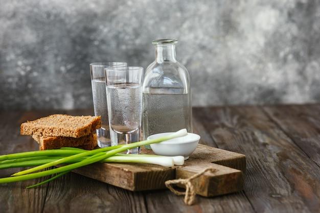Vodka con cipolla verde, pane tostato e sale sulla tavola di legno Foto Gratuite