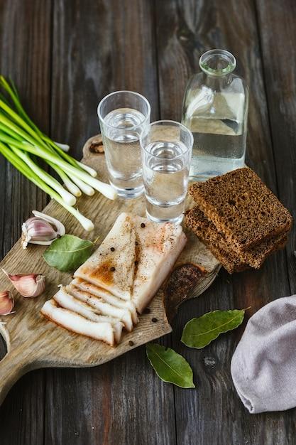Vodka con lardo e cipolla verde sulla tavola di legno Foto Gratuite