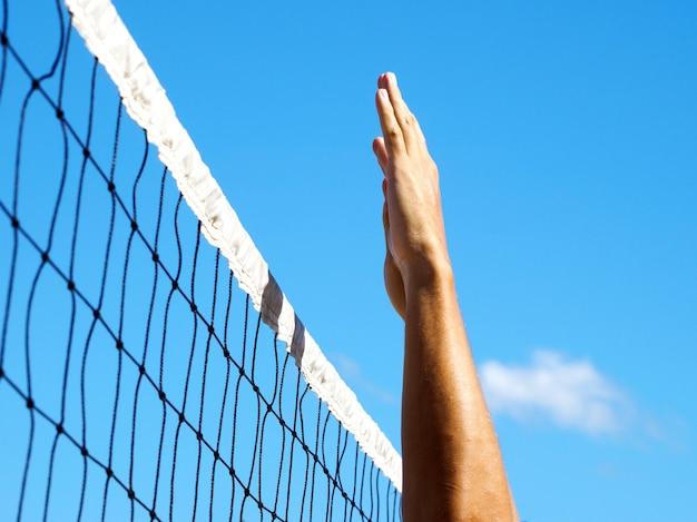 熱帯のビーチでバレーボールネット。男性の手がボールを打ちました。 Premium写真