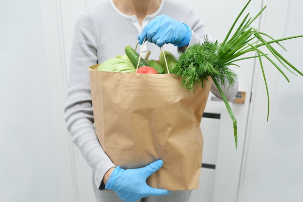 Volunteer in blue gloves holds food donation package vegetables to help the poor. donat box with foodstuffs Premium Photo