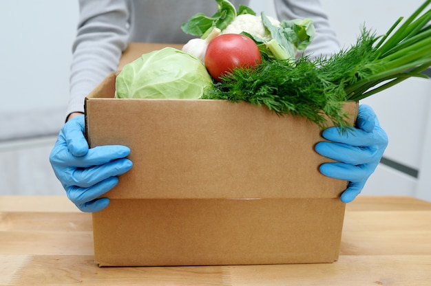 Volunteer in gloves holds food donation box vegetables to help the poor. donat box with foodstuffs Premium Photo