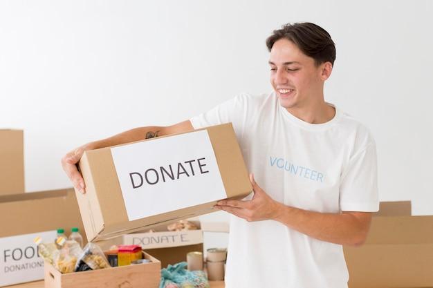 Волонтер держит коробку для пожертвований Бесплатные Фотографии