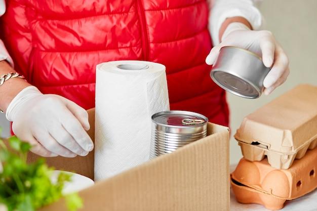 Доброволец в защитной медицинской маске и перчатках кладет еду в ящик для пожертвований. Premium Фотографии