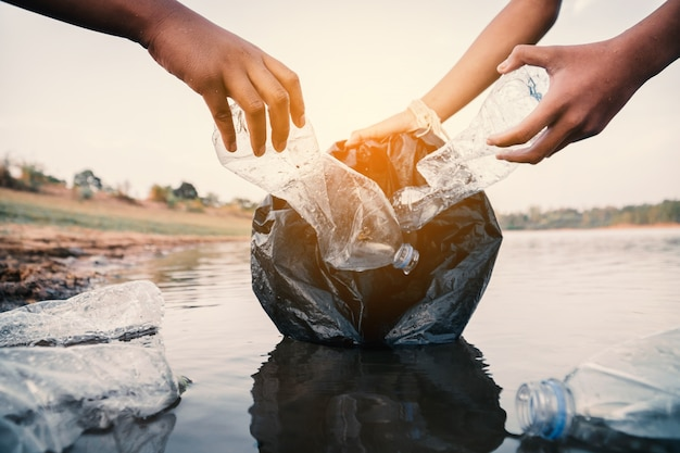 The volunteer picking up a bottle plastic in the river , protect environment from a pollution concept. Premium Photo