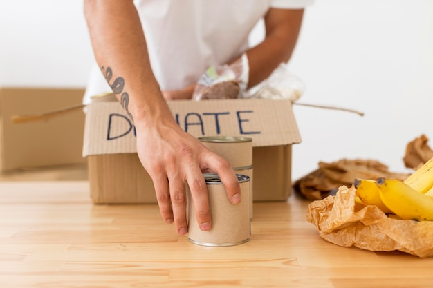 Volontario mettendo lattine con il cibo in scatole di close-up Foto Gratuite