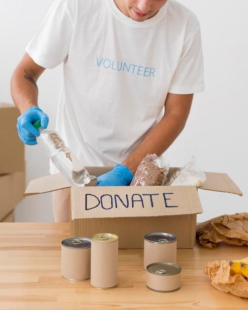 Волонтеры кладут подарки в коробки для пожертвований Premium Фотографии